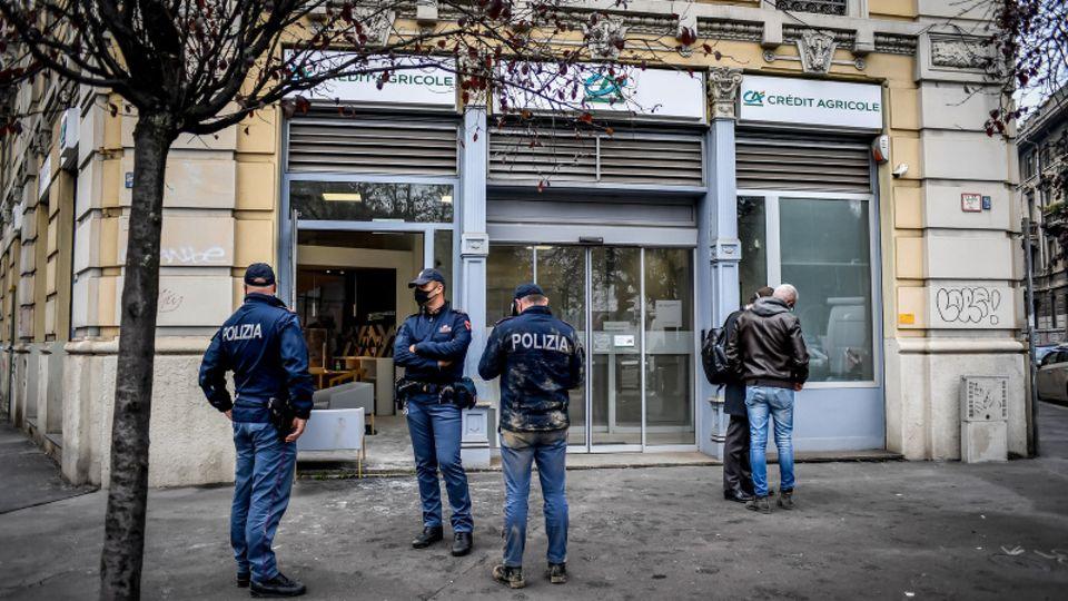 Nach einem Banküberfall in Mailand bewachen Polizisten eine Filiale der Bank Credite Agricole.