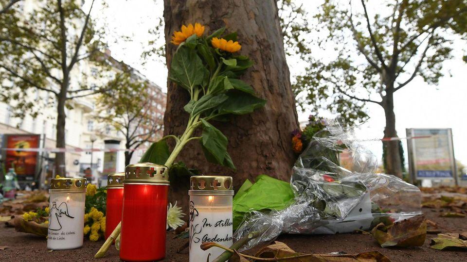 Kerzen und Blumen liegen im Bereich des Tatorts einer Terror-Attacke zum Gedenken an die Opfer