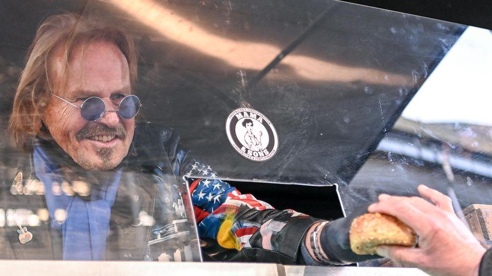 Frank Zander reicht durch eine Öffnung in einer Plexiglasscheibe ein Brötchen an