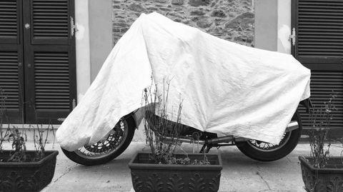 Eine Plane schützt das Motorrad im Freien