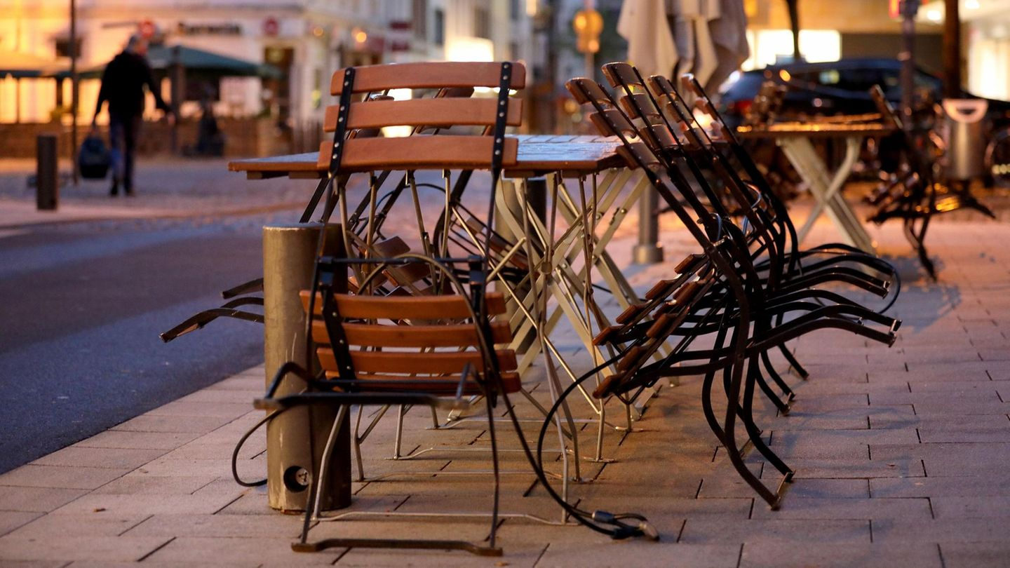 Chairs and tables are put together in the Morning in front of a restaurant in Cologne