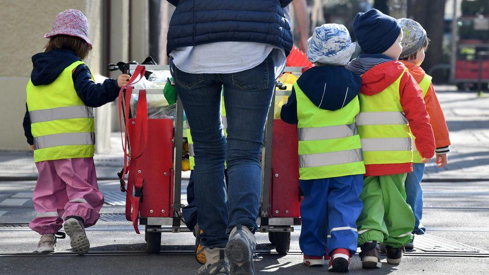 Safe-Kids-Studie: Kita-Kinder und eine Erzieherin laufen auf einem Gehweg