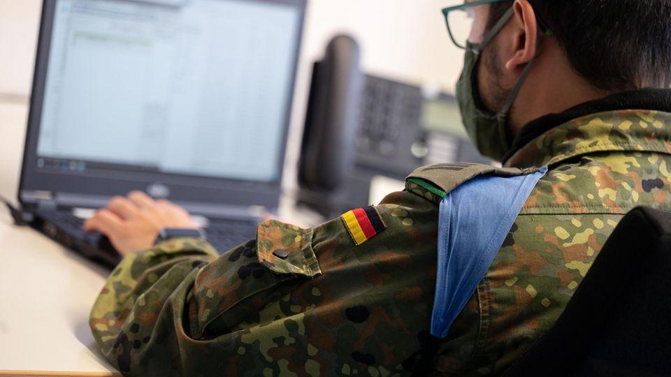 Ein Soldat sitzt vor einem Computer.