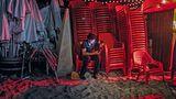 Nach Einbruch der Dunkelheit sammeln afrikanische und asiatische Arbeiter die Strandstühle und Sonnenschirme ein.
