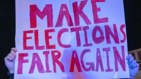 """Ein Trump-Anhänger mit einem Plakat """"Make Elections Fair Again"""""""