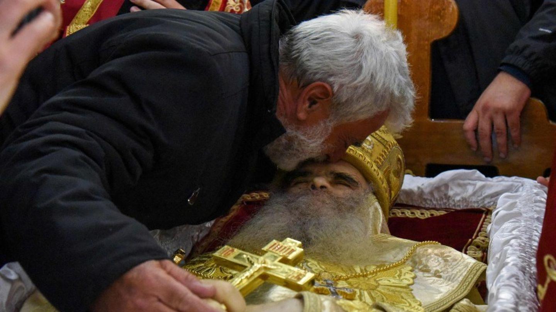 Ein Trauergast beugt sich dicht über den aufgebahrten Leichnam des Bischofs.