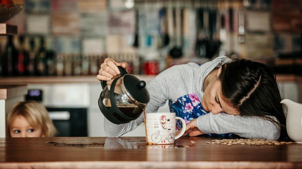 Eine müde Mutter schenkt sich Kaffee ein und verfehlt die Tasse