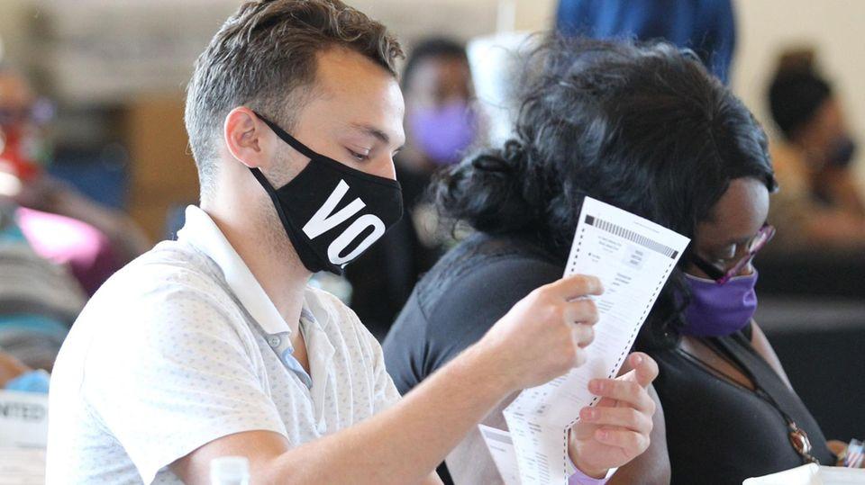 Ein junger weißer Mann und eine übergewichtige schwarze Frau sitzen nebeneinander und halten Wahlzettel in den Händen