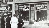 9. November 1938: Als Diskriminierung in systematische Vernichtung überging  Passanten stehen im November 1938 in einer Stadt in Deutschland vor einem jüdischen Geschäft, dessen Schaufensterscheiben in der Reichspogromnachtam 9. November1938 zerstört wurden.DieNovemberpogrome markieren den Übergang von der Diskriminierung der deutschen Juden ab 1933 hin zu ihrer systematischenVertreibungund Vernichtung.Mehr als 1400Synagogenund tausende Geschäfte, Wohnungen undjüdische Friedhöfewurden in der Nacht vom 9. auf den 10. November zerstört. Ab dem 10. November wurden ungefähr 30.000 Juden inKonzentrationslager eingesperrt.