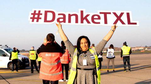 """Auf dem Vorfeld hält eine Frau ein Schild mit dem Hashtag """"Danke-TXL"""" in dieLuft, während im Hintergrund Hubschrauber der Bundespolizei zum Abschied vorbeifliegen."""