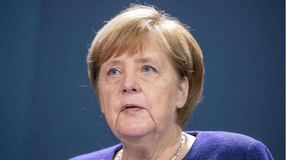 In einem blau-violetten Oberteil steht Angela Merkel vor einer blauen Wand und spricht in zwei kleine schwarze Mikrofone