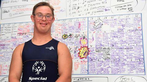 Chris Nikic steht in seinem Zimmer vor einer Tafel auf der er seine Traingseinheiten notiert hat
