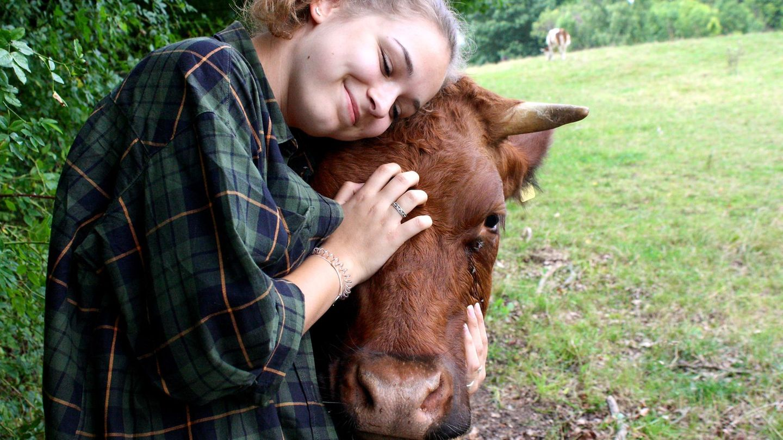 Ein Mädchen kuschelt mit einer Kuh.