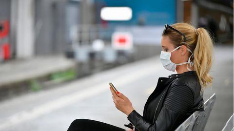 Eine junge Frau mit blondem Pferdeschwanz und Mund-Nasen-Schutz sitzt auf einer Bank und schaut auf ihr Smartphone