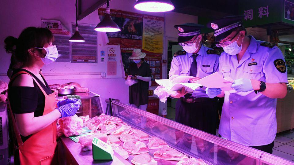 Mitarbeiter der Marktregulierungsverwaltung überprüfen in Peking das Fleisch an einem Marktstand