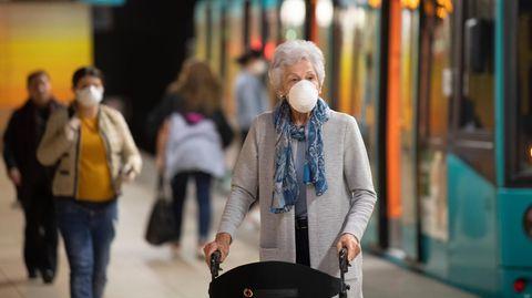 Mit einer Maske schützt sich diese Frau an der Hauptwache in Frankfurt gegen das Coronavirus