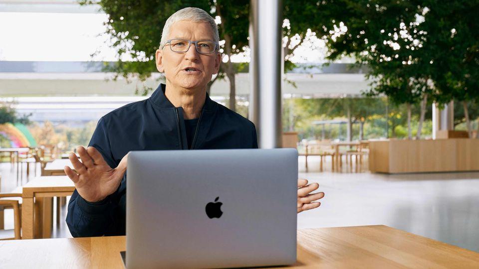 Apple-Chef Tim Cook sitzt an einem der neuen Macbooks mit eigens entwickeltem Prozessor