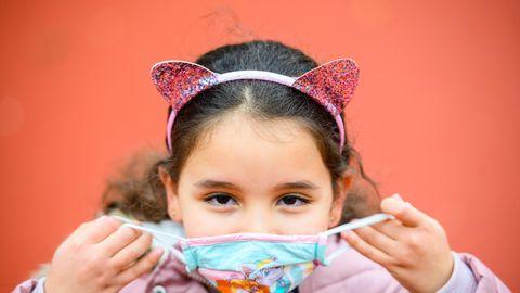 Eine Grundschülerin mit langen, braunen Locken setzt sich eine hellblaue Maske auf. Sie trägt einen Haarreif mit Glitzer-Ohren