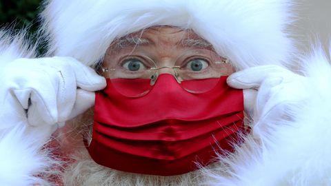 Ein Weihnachtsmann mit weißem Bart und weißer Kapuze trägt eine rote Gesichtsmaske