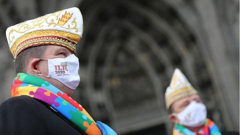 Vor dem Portal des Kölner Doms ist ein Mann mit Karnevals-Hut im Profil zu sehen. Der Mann trägt Mund-Nasen-Schutz