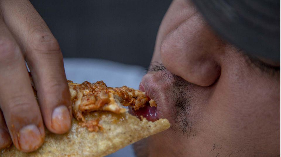 """Ein Mann isst eine """"Quesadilla"""" auf der Straße."""
