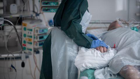 Eine Pflegekraft in Schutzkleidung hält den rechten Unterarm eines beatmeten Corona-Patienten auf der Intensivstation