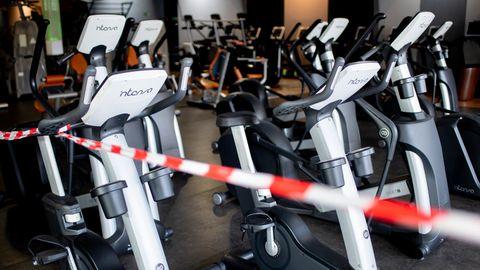Ein rot-weißes Flatterband ist an Fahrradtrainern befestigt, die in einem Fitnessstudio stehen