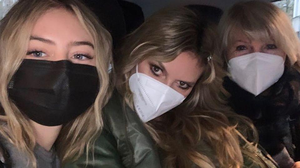 Vor einem dunklen Hintergrund sitzen drei Frauen mit weißen Masken: Leni Klum links, Heidi Klum in der Mitte und Erna rechts
