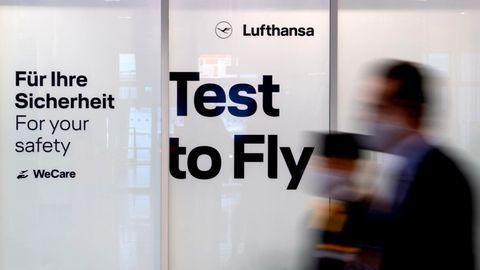 Mitarbeiter von Lufthansa laufen am Flughafen München an einem Covid-19 Testcenter vorbei.