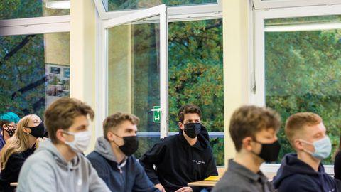 Hamburger Oberstufenschüler sitzen bei geöffneten Fenstern mit Maske im Unterricht