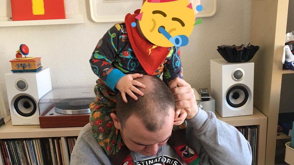 Zeichner Tobias Vogel sitzt am Laptop und hat seinen Sohn auf den Schultern