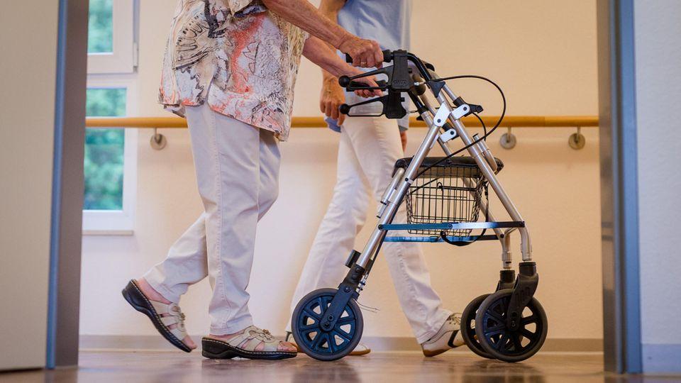 Eine Pflegekraft geht in einem Pflegeheim mit einer älteren Dame über einen Korridor (Symbolbild).