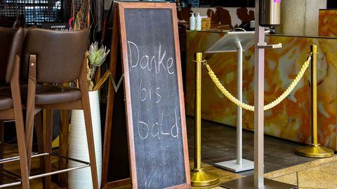 """Eine Tafel mit der Aufschrift """"Danke bis bald""""steht vor einem geschlossenen Lokal in Österreich"""