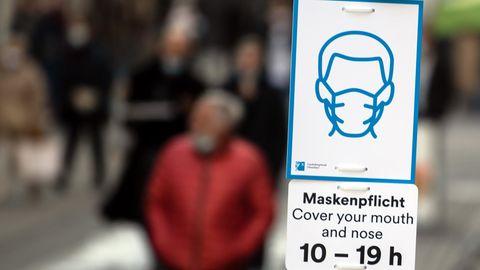 Ein Schild weist auf die Pflicht zum Tragen von Schutzmasken hin
