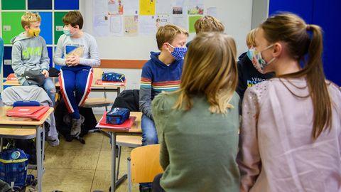 Schülerinnen und Schüler mit Mund-Nasen-Schutz gegen das Coronavirus im Schulunterricht