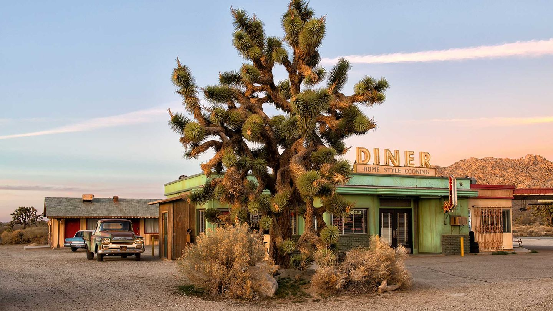 """Bild 1 von 13 der Fotostrecke zum Klicken Eine typische Kombination von Diner und Tankstelle am Highway-Rand, die Heribert Niehues in der kalifornische Mojave-Wüste für den Bildband """"Poesie der Vergänglichkeit"""" fotografierte."""