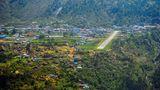 """Nepal: Tensing-Hillary Airport in Lukla (LUA)  Andreas Fecker nennt diesen Flughafen in der Nähe des Mount Everest """"einer der anspruchsvollsten Airports der Welt"""". Kein Wunder, denn die Piste ist 527 Meter kurz, hat eine Steigung von fast 20 Prozent und beginnt vor einem Felsvorsprung."""