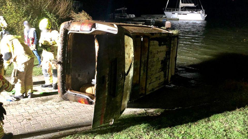 Nachrichten aus Deutschland: verdreckter VW-Bus liegt auf der Seite am Ufer eines Sees