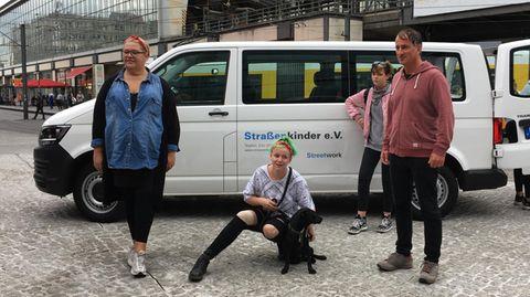 """Ilka Bessin und """"Straßenkind Toni"""" posieren für denRTL-Spendenmarathon vor einem Bus des Vereins Straßenkinder e.V."""