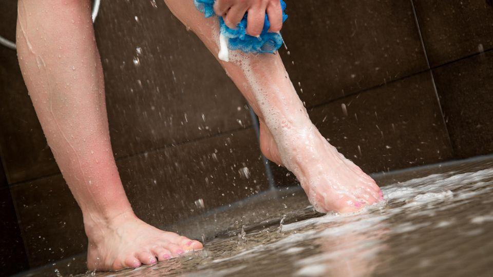Frau wäscht sich unter der Dusche