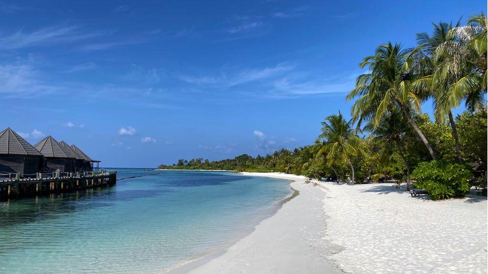 Fußabdrücke sind am leeren Strand der Insel Kuredu, Malediven zu sehen.
