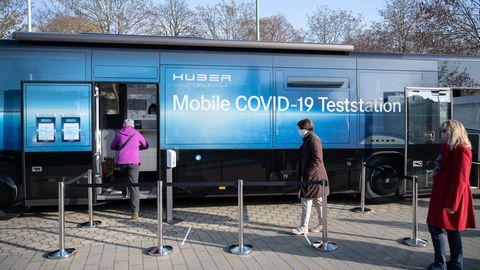 Corona-News im stern-Ticker: Drei Menschen warten vor einer mobilen Covid-19-Teststation