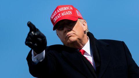 Donald Trump mit roter MAGA-Kappe und schwarzen Handschuhen zeigt in die Kamera