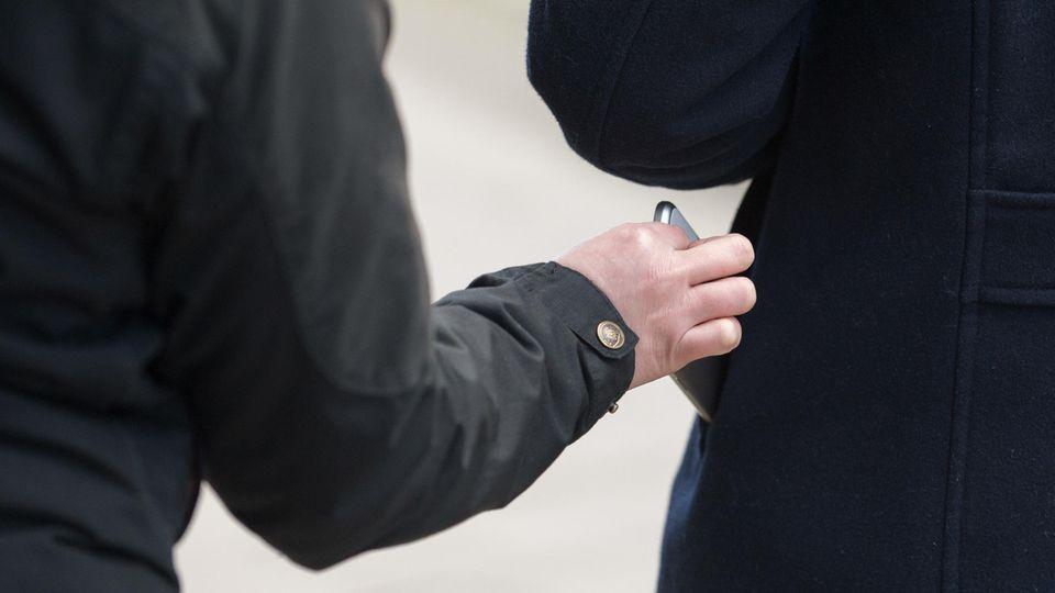 Symbolbild Taschendieb stiehlt Handy aus Jackentasche