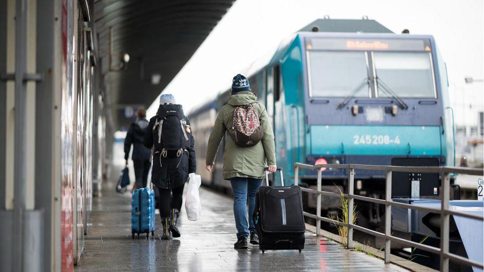Reisende gehen im Bahnhof Westerland über den Bahnsteig zu einem wartenden Zug