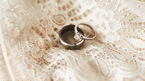 Coronavirus Hochzeit Todesfälle: Zwei Ringe liegen auf weißem Tüll