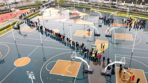 News zum Coronavirus: Auf einem Basketball-Platz stehen Menschen und warten auf den Coronatest