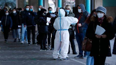 Italien, Bozen: Menschen stehen vor einer Corona-Schnelltest-Einrichtung.