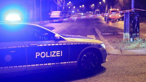 Mann attackiert Polizisten mit Messer und Dachziegeln: Polizeiwagen mit Blaulicht vor Absperrband