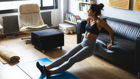Fitnessstudio geschlossen Corona: Eine Frau trainiert im Wohnzimmer